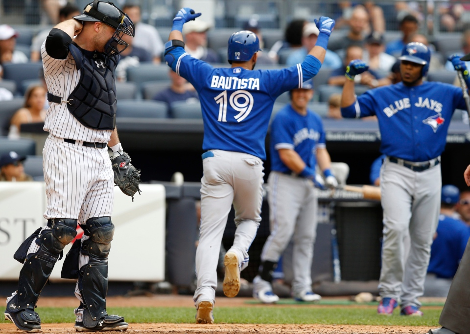 New York Yankees catcher Brian McCann, left, reacts as Toronto Blue Jays Jose Bautista (19) celebrates heading to the dugout after hitting an eighth-inning, solo, home run as on-deck-batter Edwin Encarnacion right, joins the celebration during the first baseball game of a doubleheader at Yankee Stadium in New York on Sept. 12, 2015. (Kathy Willens / AP Photo)