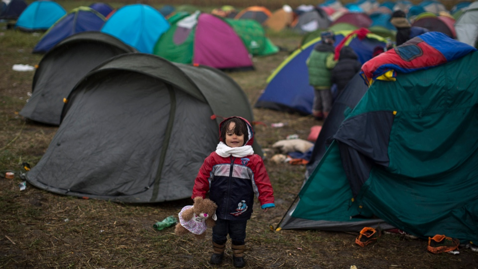 Syrian refugee child Jana Makkiyeh, 3, whose family comes from Damascus, Syria, holds a teddy bear while standing near her family's tent at a makeshift camp for asylum seekers in Roszke, southern Hungary, Thursday, Sept. 10, 2015. (AP / Muhammed Muheisen)