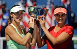 Martina Hingis, of Switzerland, left, and Sania Mirza, of India, hold up the championship trophy after defeating Casey Dellacqua, of Australia, and Yaroslava Shvedova, of Kazakhstan, in the women's doubles championship match of the U.S. Open tennis tournament on Sept. 13, 2015, in New York. (David Goldman / AP Photo)