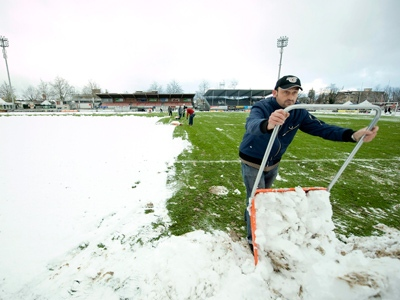 Workers clear the field at the Lachen soccer stadium in Thun, Switzerland, Saturday, Nov. 22, 2008. (AP / Keystone, Peter Schneider)