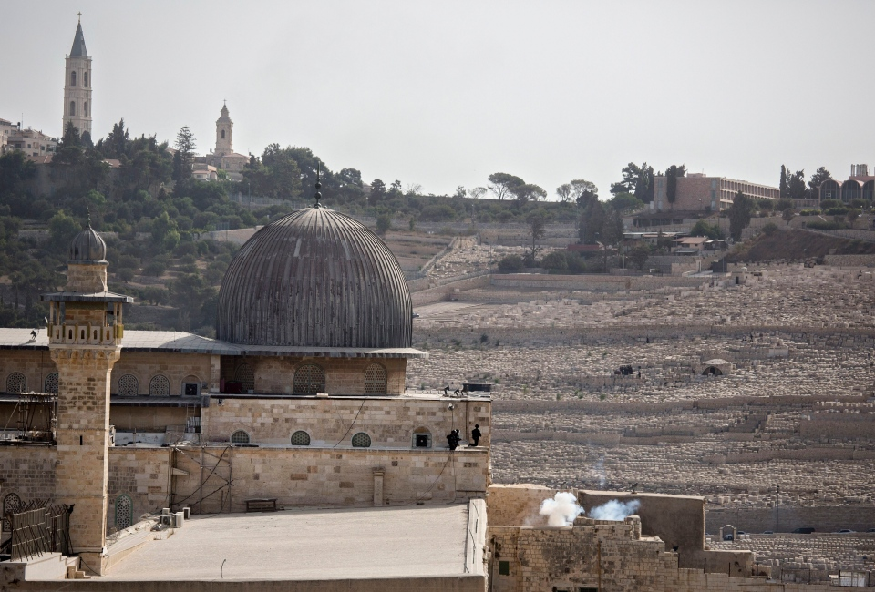Israeli border police are seen inside the Al Aqsa Mosque compound after firing tear gas or a smoke grenade in Jerusalem's Old City on Sunday, Sep. 13, 2015. (AP / Tsafrir Abayov)