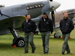 Britain's Prince Harry (right) walks with Nathan Forster, right, and Corporal Alan Robinson, of the Endeavor Fund Scholars, past Battle of Britain aircraft at Goodwood Aerodrome in West Sussex, England, Tuesday, Sept. 15, 2015. (AP/Kirsty Wigglesworth, Pool)