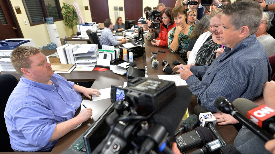 Rowan County Deputy Clerk Brian Mason, left, asks Shannon Wampler-Collins, right and her partner Carmen Wampler-Collins to double check their marriage license at the Rowan County Judicial Center in Morehead, Ky. Monday, Sept. 14, 2015. (AP / Timothy D. Easley)