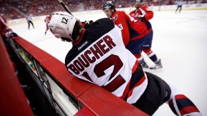 The New Jersey Devils' Reid Boucher (12) is knocked into the boards by the Washington Capitals' Tom Wilson (43) in the third period of an NHL hockey game, in Washington, on Thursday, March 26, 2015. (THE CANADIAN PRESS/AP Photo/Alex Brandon)