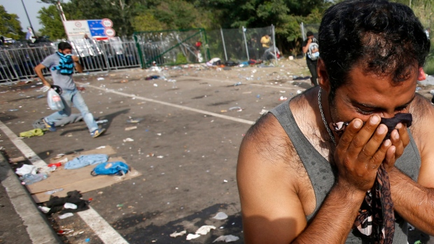 A migrant reacts after a protest at the 'Horgos 2' border crossing into the Hungary, near Horgos, Serbia, Wednesday, Sept. 16, 2015. (AP / Darko Vojinovic)