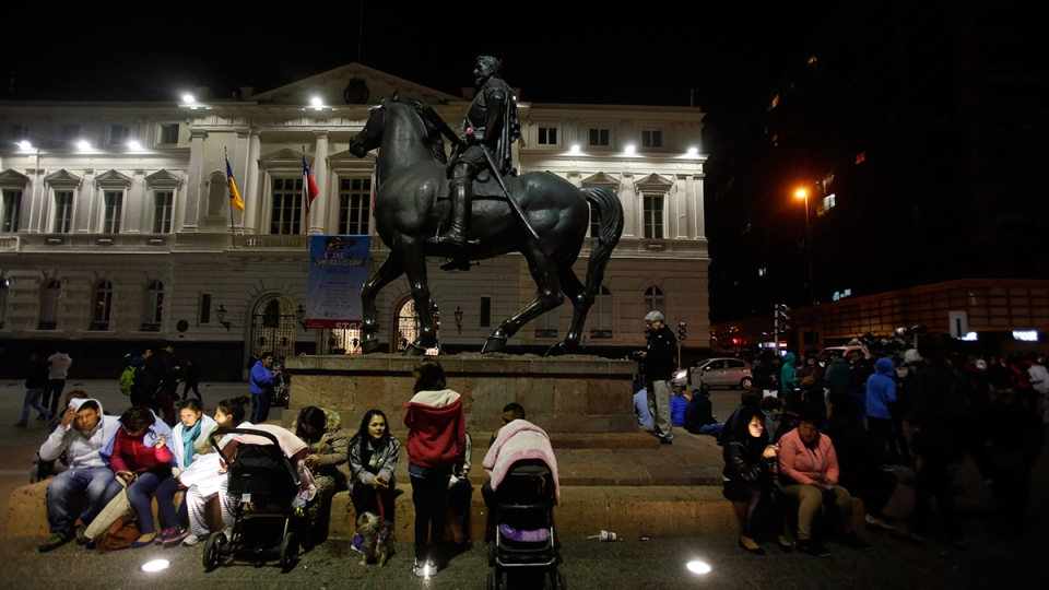 Residents sit next to an equestrian statue, in Santiago's main square after an 8.3-magnitude earthquake, in Santiago, Chile, Wednesday, Sept. 16, 2015. (AP / Luis Hidalgo)