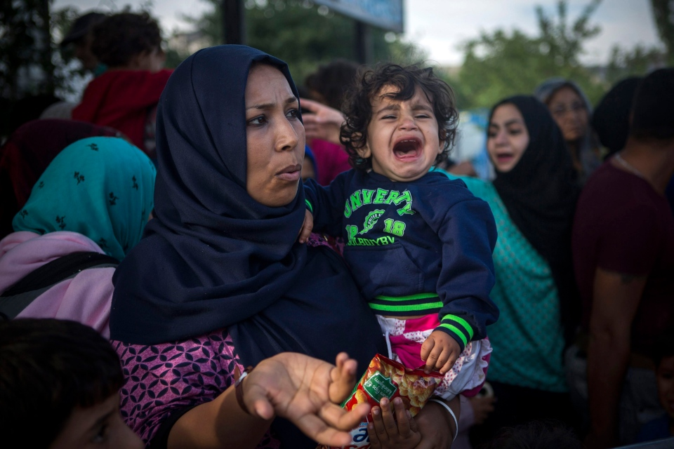 A baby cries as she waits with her mother to be registered by police in the southern Serbian town of Presevo, Friday, Sept. 11, 2015. (AP / Santi Palacios)