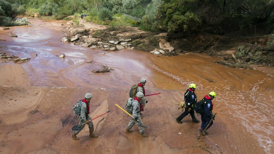 Search and rescue volunteers walk in Short Creek while looking for a missing person in Colorado City, Ariz. on Sept. 16, 2015. Flash flooding in the area killed at least 18 people. (Michael Chow / The Arizona Republic)