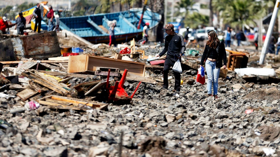 People walk through debris left behind by an earthquake-triggered tsunami in the coastal town of Coquimbo, Chile, Thursday, Sept. 17, 2015. (AP / Luis Hidalgo)