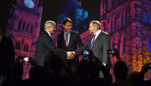 NDP leader Tom Mulcair shakes hands with Conservative leader Stephen Harper as Liberal leader Justin Trudeau looks on during their introduction prior to the leaders' debate in Calgary on Thursday, September 17, 2015. (Sean Kilpatrick / THE CANADIAN PRESS)