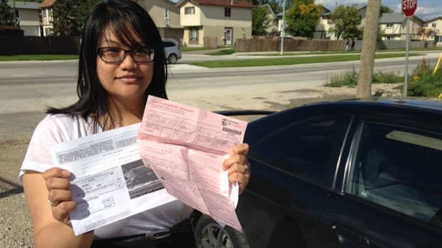 Christine Ibalio holds up her two tickets issued separately for what she believes is one offence.