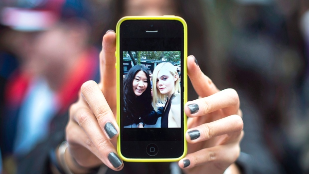 Samantha Ma shows off her selfie with actress Elle Fanning during the 2015 Toronto International Film Festival in Toronto on Saturday, September 12, 2015. (THE CANADIAN PRESS / Darren Calabrese)