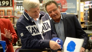 Prime Minister Stephen Harper compares his hat to some blue paint with local candidate Harold Albrecht (right) during a campaign stop at a hardware store in St. Jacobs, ON. Monday, Sept. 21, 2105. (Ryan Remiorz / THE CANADIAN PRESS)