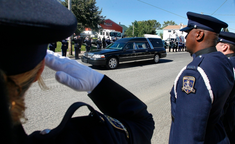 Members of the Halifax Regional Police Service salute the hearse as it approaches First Presbyterian Church prior to the funeral of slain Truro Police Officer Catherine Campbell in Stellarton, N.S. on Monday, Sept. 21, 2015. (THE CANADIAN PRESS / Darren Pittman)