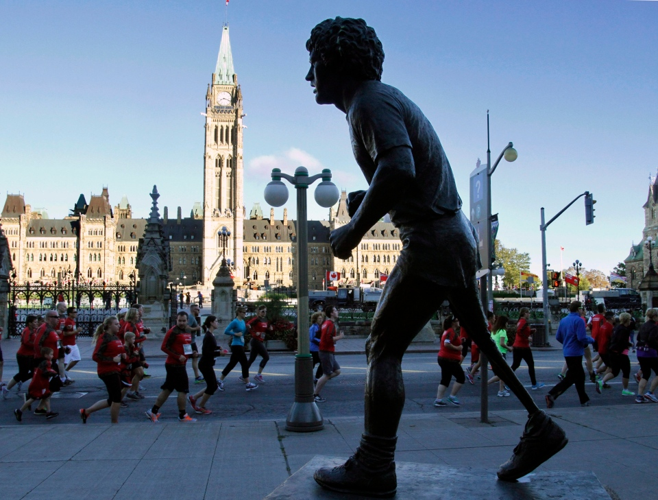 Participants taking part in the Army Run, to raise funds and awareness to aid families of ill, injured and disabled soldiers run past the statue of Terry Fox, during a run, walk or roll event in Ottawa, Sunday, September 20, 2015. THE CANADIAN PRESS/Fred Chartrand