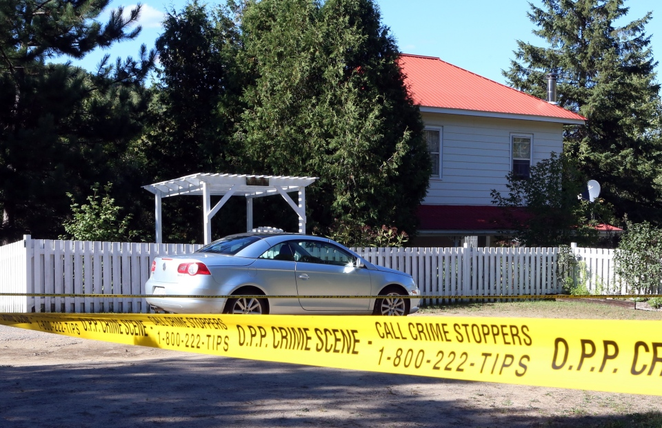 Police crime scene tape surrounds a house in Wilno, Ont., Tuesday, Sept.22, 2015. Ontario Provincial Police investigating a fatal shooting in a small community west of Ottawa say they are now investigating three homicides.THE CANADIAN PRESS/Fred Chartrand