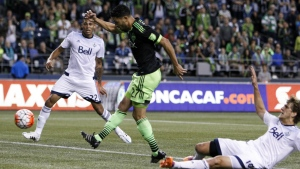 Seattle Sounders midfielder Lamar Neagle, centre, shoots and scores between Vancouver Whitecaps defenders Christian Dean, left, and Diego Rodriguez during the first half of a CONCACAF Champions League soccer match in Seattle on Sept. 23, 2015. (AP / Jennifer Buchanan)