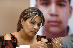 FILE - In this July 29, 2014, file photo, Araceli Rodriguez handles a rosary during a news conference in Nogales, Mexico, that belonged to her son Jose Antonio Elena Rodriguez, pictured behind her, who was shot and killed by U.S. Border Patrol agent in October 2012.