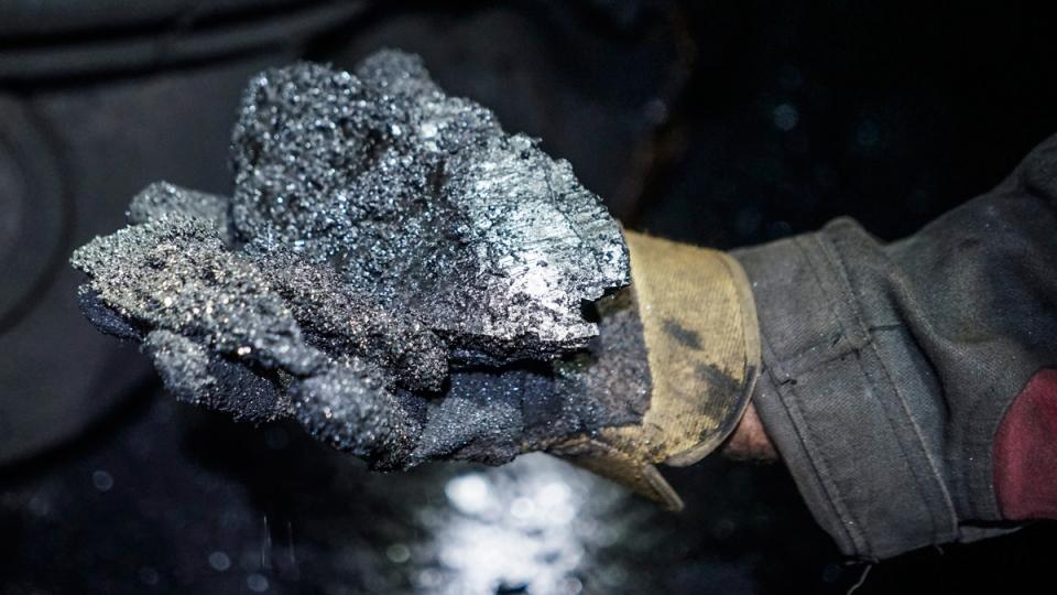 A miner shows a lump of coal. (Mstyslav Chernov / AP)