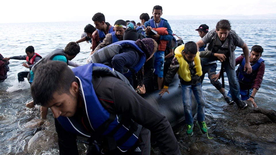 Afghan migrants arrive on the shores of the Greek island of Lesbos after crossing the Aegean Sea from Turkey on an inflatable dinghy, Thursday, Sept. 24, 2015. (AP / Petros Giannakouris)