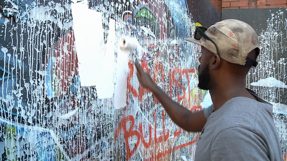 Ottawa artist Kalkidan Assefa paints over his own mural which was defaced sometime overnight. Sept. 24, 2015