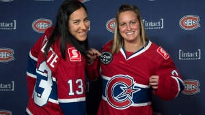 In this file photo, Caroline Ouellette, left, and Marie-Philip Poulin show off their Montreal Canadiennes jerseys Thursday, September 24, 2015, in Montreal. (Paul Chiasson / THE CANADIAN PRESS)