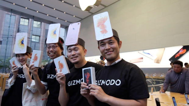 From left, Makiko Maeda, Hisanori Kogure, Nobuhiko Matsuba, and Naoki Tsukamoto show their iPhone 6s after purchasing at an Apple store in Tokyo as Apple Inc. launched the sales of the latest models of its popular smartphone in Japan Friday, Sept. 25, 2015. (AP / Koji Sasahara)