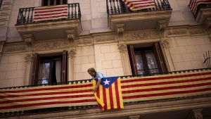 """In this Wednesday, Sept. 23, 2015 photo, a woman attaches an """"estelada"""" or pro independence flag on her balcony in Barcelona, Spain. (AP / Emilio Morenatti)"""