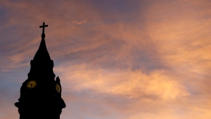 Clouds are lit by the rising sun over St. Augustine Roman Catholic Church in Philadelphia, on Sept. 27, 2015. (AP / Julio Cortez)