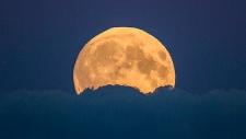 A full moon rises between clouds in Berlin, Germany, Sunday, Sept. 27, 2015. (AP / Gero Breloer)
