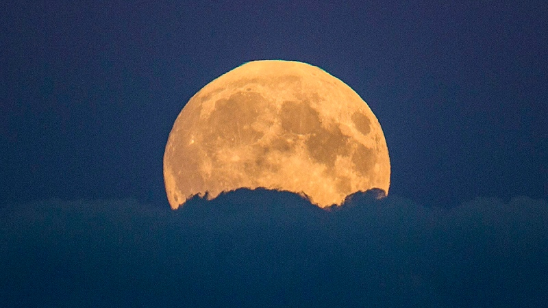 A full moon rises between clouds in Berlin, Germany, Sunday, Sept. 27, 2015. (AP / Gero Breloer)