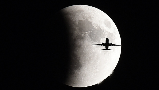 A plane flies in front of the supermoon during a lunar eclipse in Geneva, Ill., Sunday, Sept 27, 2015. (Jeff Knox / Daily Herald)