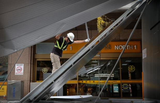 A construction crew member removes fallen scaffolding from Typhoon Dujuan at the main train station in Taipei, Taiwan, Tuesday, Sept. 29, 2015. (AP / Wally Santana)