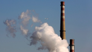 In this Nov. 13, 2014 file photo, a passenger airliner flies past a coal-fired power plant in Beijing, China. (AP / Andy Wong, File)