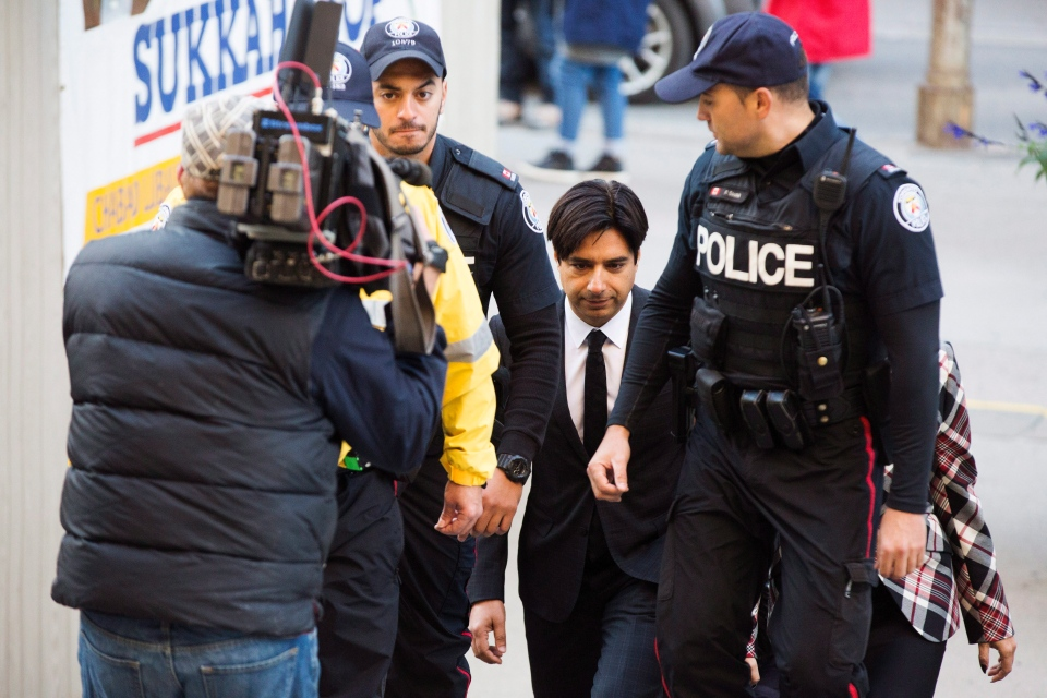 Former CBC radio host Jian Ghomeshi, centre, arrives to appear for a pre-trial hearing for his sexual assault case, in Toronto, on Thursday, October 1, 2015. (Michelle Siu / THE CANADIAN PRESS)