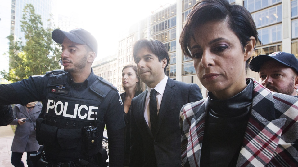 Police escort former CBC radio host Jian Ghomeshi, centre, who appears with his lawyer Marie Henein, right, for his pre-trial hearing for his sexual assault case in Toronto on Thursday, Oct. 1, 2015. (Michelle Siu / THE CANADIAN PRESS)
