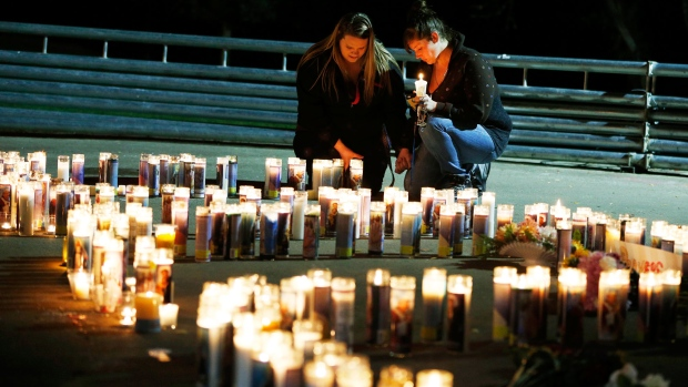 Meriah Calvert, left, of Roseburg, Ore., and an unidentified woman pray by candles spelling out the initials for Umpqua Community College after a candlelight vigil Thursday, Oct. 1, 2015, in Roseburg, Ore. (AP / John Locher)