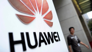 A man walks near a logo at a R&D centre of Huawei Technologies Inc. in Wuhan, in central China's Hubei province on Monday, Oct. 8, 2012. (AP)