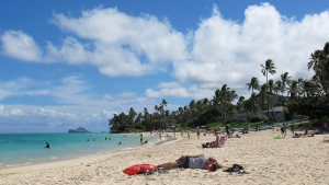 This Oct. 29, 2013 photo shows people at Lanikai Beach in Kailua, Hawaii. (AP Photo/Audrey McAvoy)