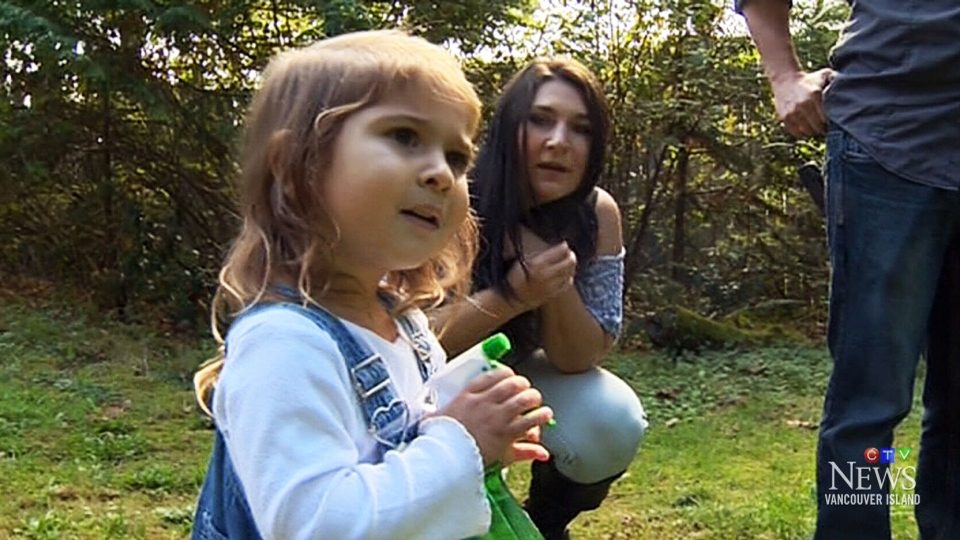 Two-year-old Mya Watson sprays away monsters hiding in her backyard in Sooke, B.C.