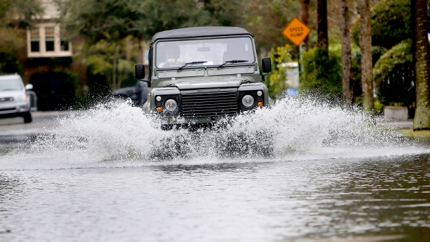 A vehicle navigates the flood water after high tides and heavy rains left parts of downtown Charleston, S.C., underwater Friday, Oct. 2, 2015. Millions along the East Coast breathed a little easier Friday after forecasters said Hurricane Joaquin would probably veer out to sea. But a freakishly powerful rainstorm fueled in part by the hurricane threatened to bring ruinous flooding to parts of the Atlantic Seaboard over the weekend. (The Post And Courier via AP / Paul Zoeller)