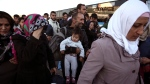 Migrants and refugees rush to get on a bus which will transfer them at a metro station after their arrival from the Greek island of Lesbos at the Athens' port of Piraeus, Sunday, Oct. 4, 2015. (AP / Yorgos Karahalis)