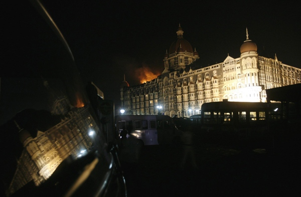 Smoke and flames rise from one of the wings of the Taj Palace Hotel, are also reflected in a car window, in Mumbai, India, Thursday, Nov. 27, 2008. Indian commandos killed the last three gunman at a landmark hotel late Thursday. (AP / Gautam Singh)
