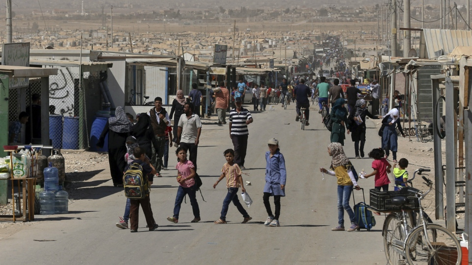 Syrian refugees stroll on the main street of the UN-run Zaatari refugee camp near Mafraq, northern Jordan on Oct. 1, 2015. (AP / Raad Adayleh)