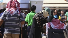 Refugees sign up for a return bus to Syria