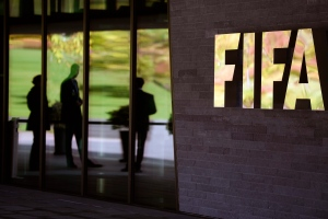 People are reflected in the entrance of the FIFA headquarters in Zurich, Switzerland, Thursday, Sept. 24, 2015, where the FIFA Executive Committee meeting takes place from Sept. 24-25, 2015. (Walter Bieri/Keystone via AP)