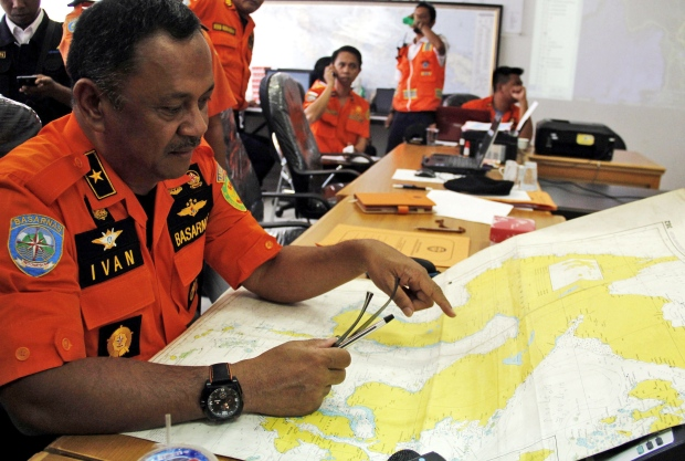 A member of the National Search And Rescue Agency (BASARNAS) examines a map of Sulawesi Island, at the crisis centre searching for the missing DHC-6 Twin Otter plane owned by Aviastar Mandiri airline, at Sultan Hasanuddin airport in Makassar, Indonesia, Monday, Oct. 5, 2015. (AP)