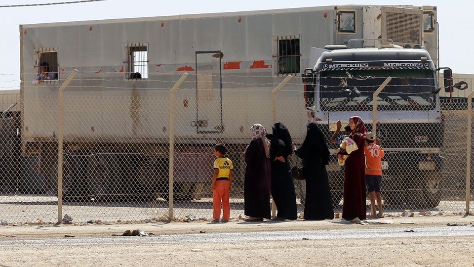 Syrian refugees stand by a fence to see their family members getting on a return bus for women and children to the Syrian border, at the UN-run Zaatari refugee camp near Mafraq, northern Jordan, Thursday, Oct. 1, 2015. (AP / Raad Adayleh)