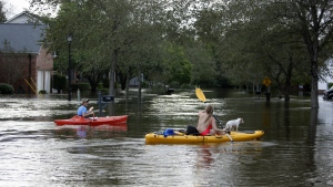 James Savage, left, and his girlfriend, Ianna Fincher, with her dog Lucy, kayak down Mayfield Street in the Ashborough subdivision near Summerville, S.C., after many of their neighbors evacuated on Oct. 5, 2015. (AP / Mic Smith)