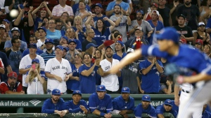 Fans cheer above the Toronto Blue Jays dugout as Roberto Osuna, foreground, pitches during the 10th inning of a baseball game against the Boston Red Sox in Boston on Sept. 8, 2015. (AP / Michael Dwyer)